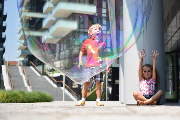 Children playing behind a large bubble